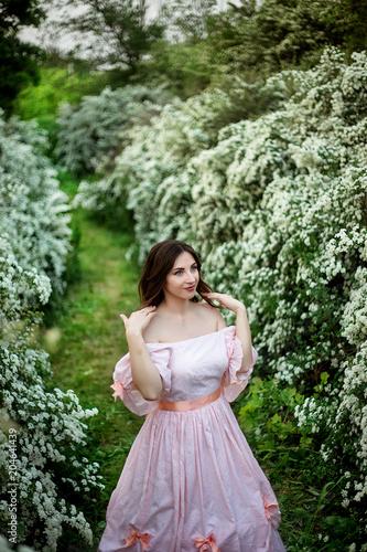 portret pięknej dziewczyny w eleganckiej sukience na tle kwitnących krzewów
