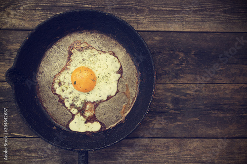 One fried egg in a frying pan on a wooden background in rustic style close-up and copy space