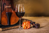 Classical old violins detail with red wine glass