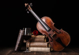 Old violin with books and red wine