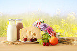 image of fruits and cheese in decorative basket with flowers over wooden table. Symbols of jewish holiday - Shavuot.