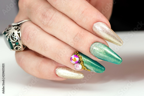 Close up of female hands showing colorful nail polish on white background. the woman is wearing green manicure.