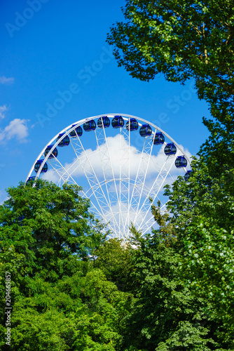 Aluminium Amusementspark Ferris wheel behind trees