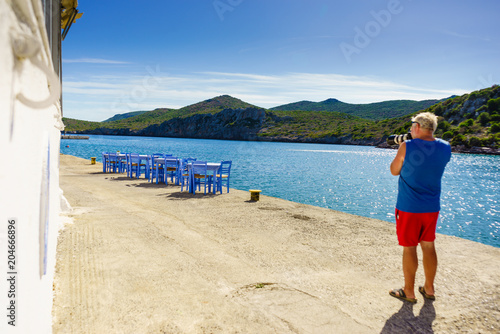 Male tourist taking picture from open cafe, Greece