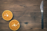 Fresh orange fruit with knife on the brown wooden table background.