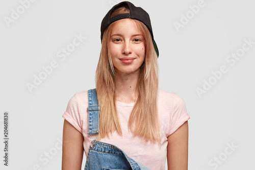 Pleased Caucasian teenage girl wears black cap and denim overalls, going to have stroll with friends, poses against white background. Youngster woman dressed in fashionable clothes. People and style - 204681830