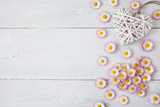 Daisies, petals and hearts on a wooden light background - 204682670