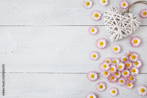 Foto Murales Daisies, petals and hearts on a wooden light background
