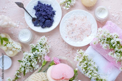 SPA. Different cosmetics for care and beauty. Pink background and white flowers. Place for text. Sea salt © Marina