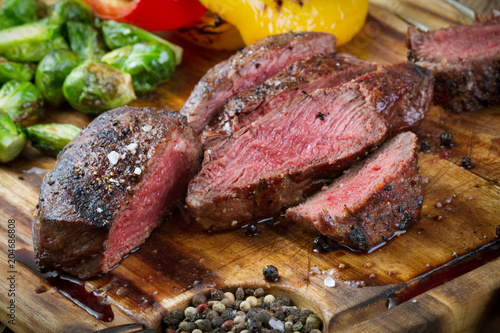 Plexiglas Steakhouse grilled and sliced beef steak with vegetables on wooden background