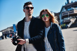 Cute couple in sunglass walking at the street with camera