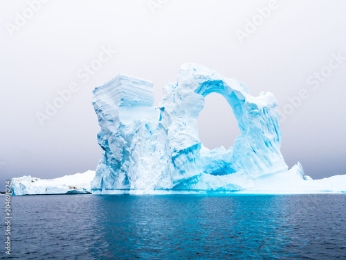 Fotobehang Antarctica Arch shaped iceberg in Pleneau Bay iceberg graveyard west of Antarctic Peninsula, Antarctica