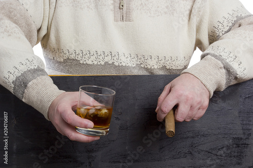 Men's hands with a cigar and whiskey