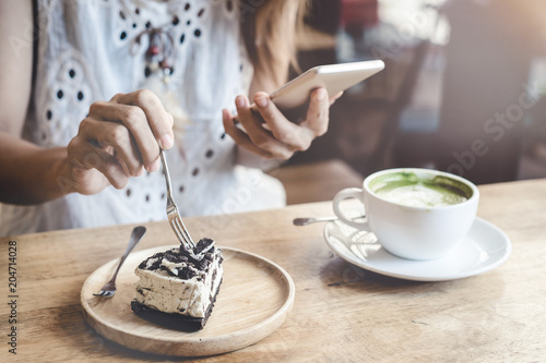 Fototapeta Young woman using smart phone and eating cake