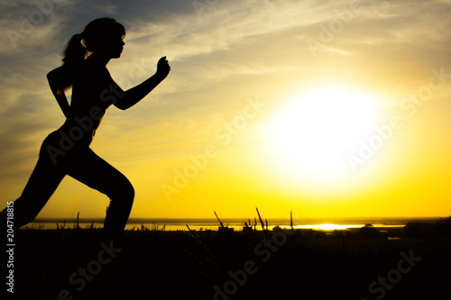 Leinwanddruck Bild silhouette of a woman jogging on nature at sunset, sports female profile, concept of sport, leisure and healthcare