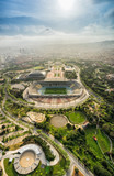 Barcelona aerial view, Anella Olimpica sport complex on the hill with city skyline , Spain. Sunbeam light