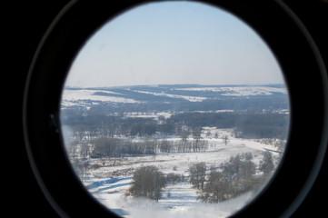 вид на заснеженную природу через круглое окно илюминатора
