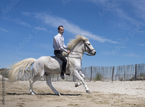 Fototapeta riding man on the beach