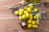 olives and bottle of extra virgin olive oil on wood - 204724831