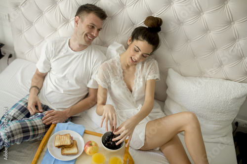 Young happy couple having breakfast in luxury room