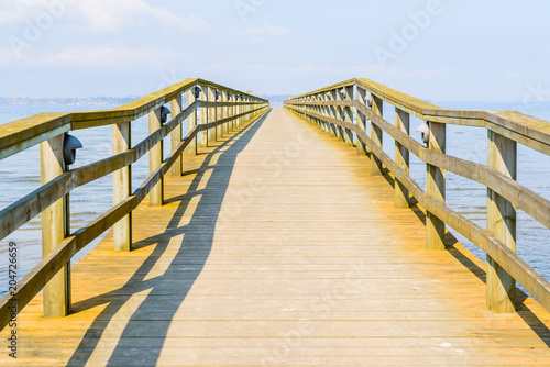 Borstahusen, Sweden - Long and empty wooden pier on a sunny day with haze.