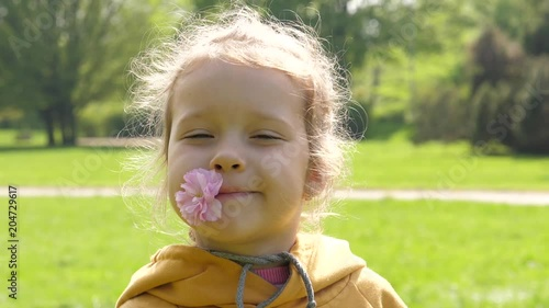 Glad happy face portrait of little girl child in park with a flower held by lips in mouth