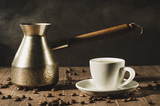 white cup and the coffeemaker with hot steam on a wooden background/white cup and the coffeemaker with hot steam on a wooden background. selective focus