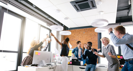 cheerful business people in smart casual wear express positive feelings in the office with loft style