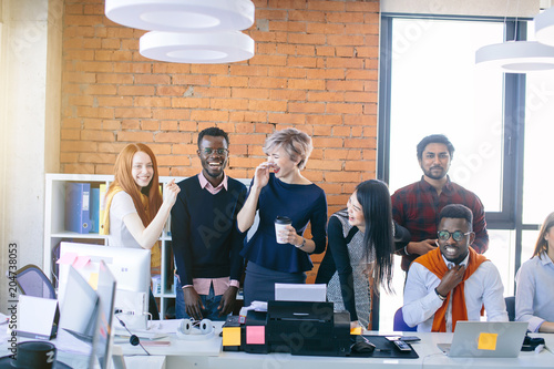 young multi ethnic people are laughing at work while their African partner feels bad. Afro man dislike his co-workers. feed up to the back teeth. Man got bellyful of colleagues