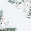 Flowers composition. Frame made of cotton flowers and eucalyptus branches on pastel blue background. Flat lay, top view, square, copy space - 204740095