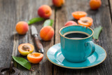 Closeup of delicious coffee and plums in summer garden
