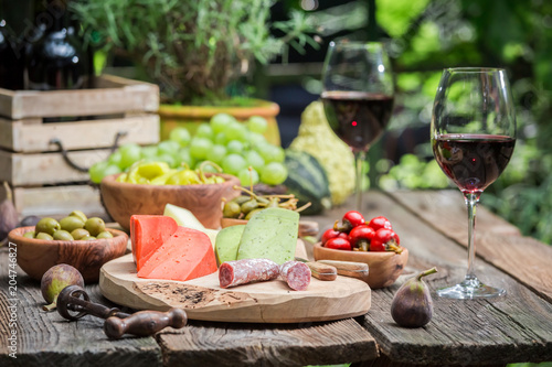 Fridge magnet Table with appetizers and wine in summer garden