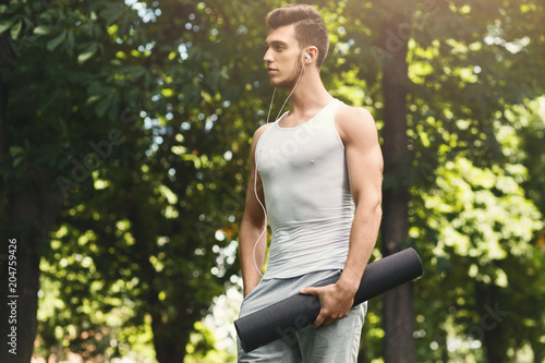 Man holding mat and listening to music in park