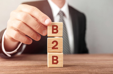 Businessman made word B2B with wood building blocks.