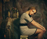 fashion model woman with creative make up sitting on a stool in drama decoration