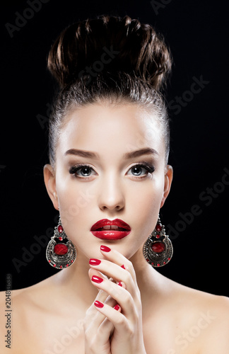 Sexy Beauty Girl with Red Lips and Nails. Luxury Woman, jewelery earrings. Fashion Brunette Portrait isolated on black background.