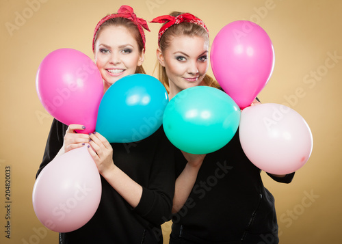 Retro girls preparing balloons birthday party.