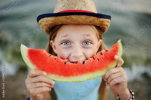 Fototapeta baby girl in the hat eagerly eats juicy watermelon on sea background