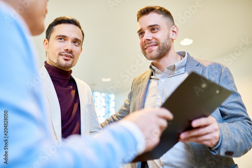 Low angle portrait of three handsome business people holding clipboard and smiling while discussing financial strategies in modern office building