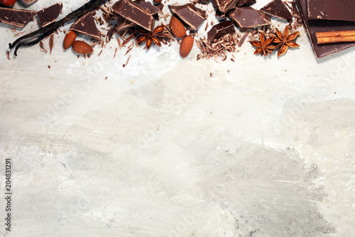 Poster dark chocolate bars  with anise and nutson stone table and broken pieces of cocoa