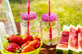 picnic table with juicy fruits and delicious lemonade in a summer park