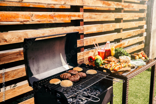 Wall mural Seasonal vegetables and burgers cooked outdoors on grill