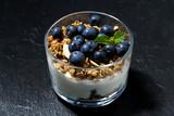 dessert with fresh blueberries, granola and cream on dark background