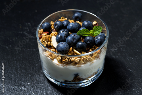 Poster dessert with fresh blueberries, granola and cream on dark background