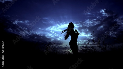 Female silhouette in night steppe and blue sky background. Concept of relaxing and lonely meditaion.