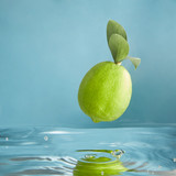 Beautiful green limes falls into water