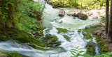 streams of clean water, Isichenko waterfall in Mezmay, Adygea, Caucasus surrounded by young green grass in the spring