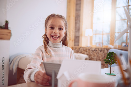 Wonderful mood. Cheerful happy girl looking at you while holding a solar battery