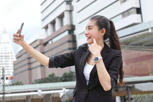 Fototapeta Cheerful young Asian woman taking a picture or selfie with mobile smart phone outdoors
