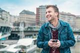 Happy young man listening music enjoying on street - 204871296